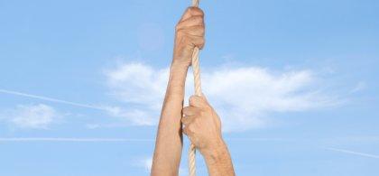 Imagen de unas manos trepando por una cuerda con el cielo azul de fondo