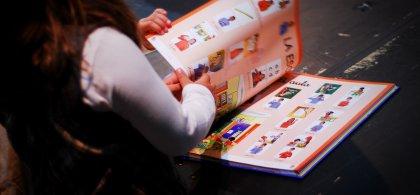 Imagen de una niña manejando un libro con pictogramas