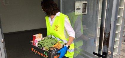 Imagen de una voluntaria de Fundación ONCE llevando una caja de comida a un domicilio
