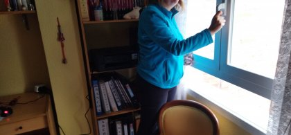 Imagen de Raquel, de pie delante de una estantería con libros y ante una ventana que va a abrir