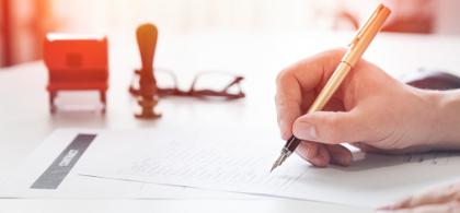 Imagen de un escritorio en la que se ve una mano escribiendo sobre un folio