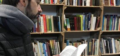 Imagen de Tomás ante un texto en una biblioteca