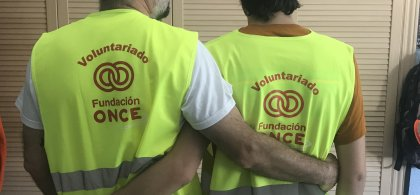 Imagen de dos personas entrelazadas por la espalda con el chaleco del voluntariado de Fundación ONCE