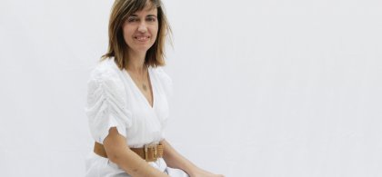 Imagen de María sentada, vestida de blanco y con las manos en las rodillas